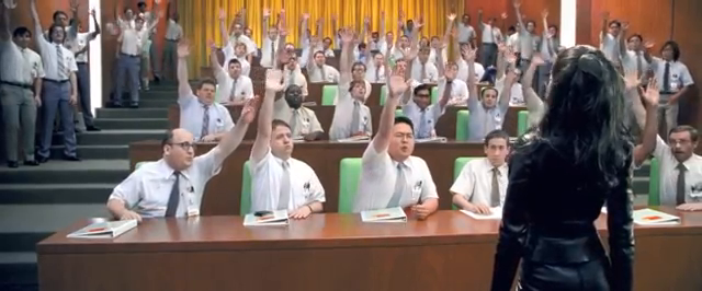 A room of men in business casual attire raising their hands in front of their teacher.
